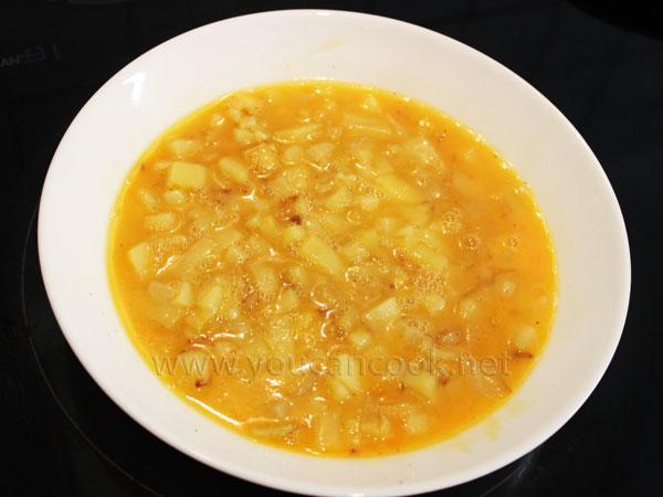 Eiermischung mit gebratenen Kartoffeln und Zwiebeln vermischen